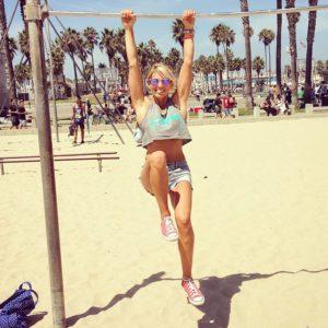 Krista Striker hanging from a horizontal bar