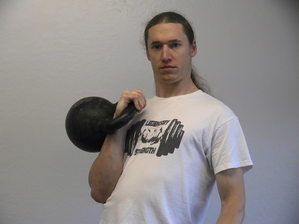 Logan Christopher carrying a kettlebell