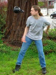 Logan Christopher juggling a kettlebell
