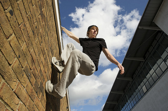 parkour athlete hanging from a wall