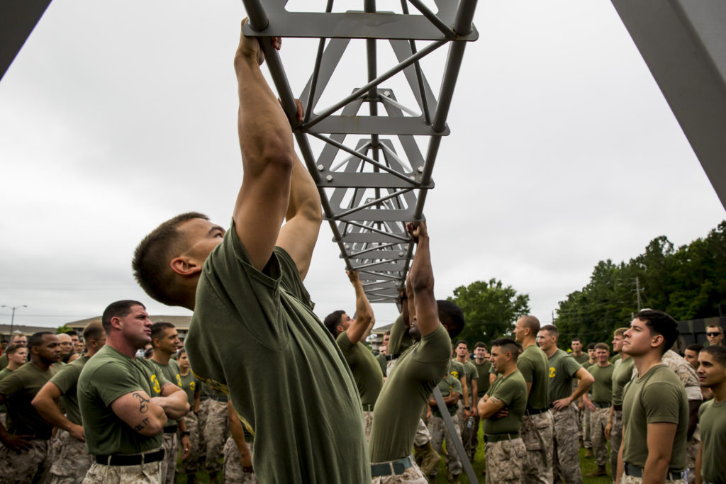 Marines with 8th Communications Battalion, 2nd Marine Expeditionary Force, compete in a pull-up competition in which they executed 300 pull-ups for time during the battalion's field meet aboard Camp Lejeune, N.C., June 5, 2015. The field meet included events such as the mile and a half relay run, 300 pull-ups for time, a tire flip relay, armored Humvee pull for 50 meters for time, a chemical, biological, radiological and nuclear relay, and a tug-of war competition. The purpose of the event was to promote unit camaraderie, friendly competition and Esprit de Corps. (U.S. Marine Corps photo by Cpl. Krista James/Released)