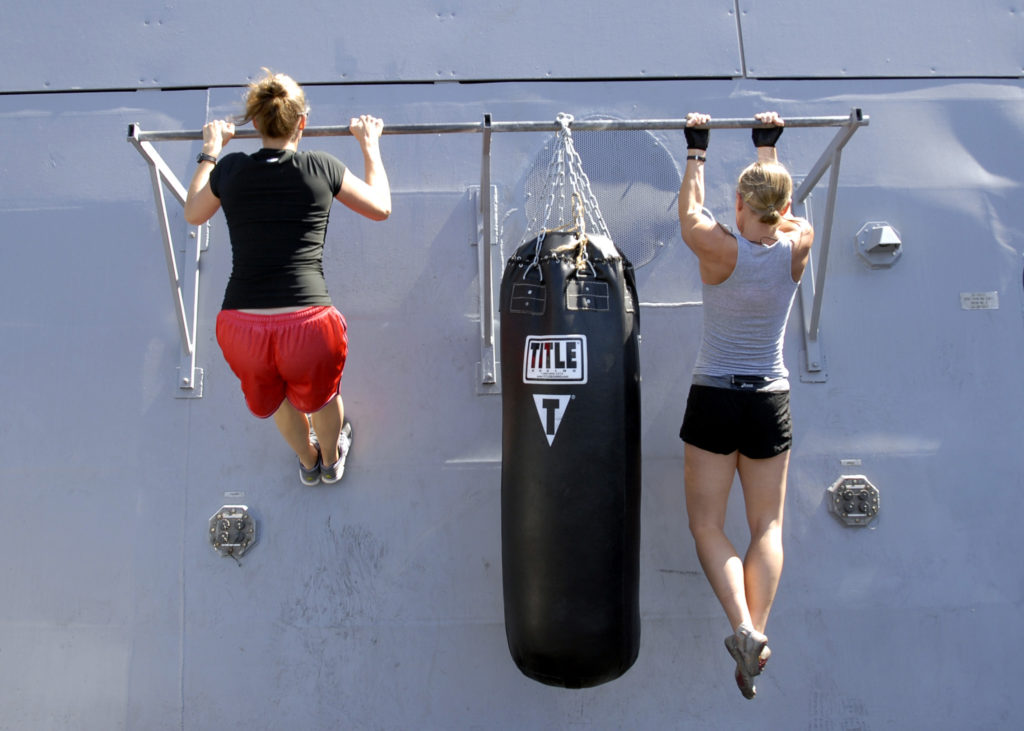 PACIFIC OCEAN (Aug. 19, 2012) Lt. j.g. Jamie Neal, left, and Lt. Carla Futchko do pull-ups as part of a workout aboard the amphibious transport dock ship USS Green Bay (LPD 20). Green Bay is part of the Peleliu Amphibious Ready Group currently underway conducting a certification exercise. (U.S. Navy photo by Mass Communication Specialist 1st Class Elizabeth Merriam/Released) 120819-N-BB534-256 Join the conversation https://www.facebook.com/USNavy https://www.twitter.com/USNavy https://navylive.dodlive.mil